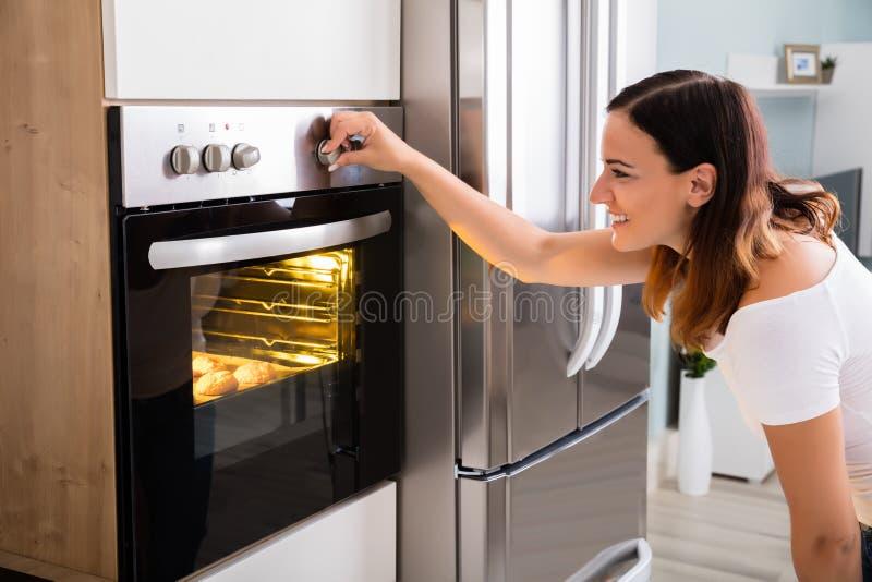 Kvinna som använder mikrovågen Oven In Kitchen royaltyfri fotografi