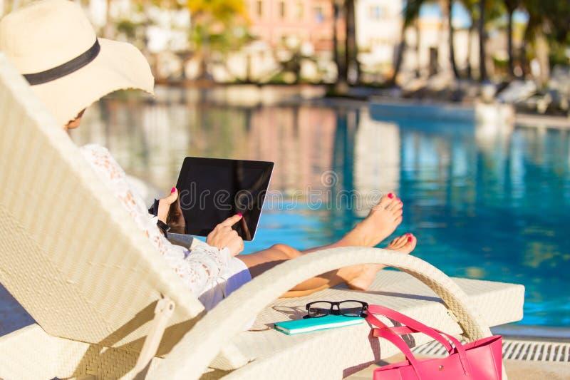Kvinna som använder minnestavladatoren på semester i lyxig semesterort arkivfoton