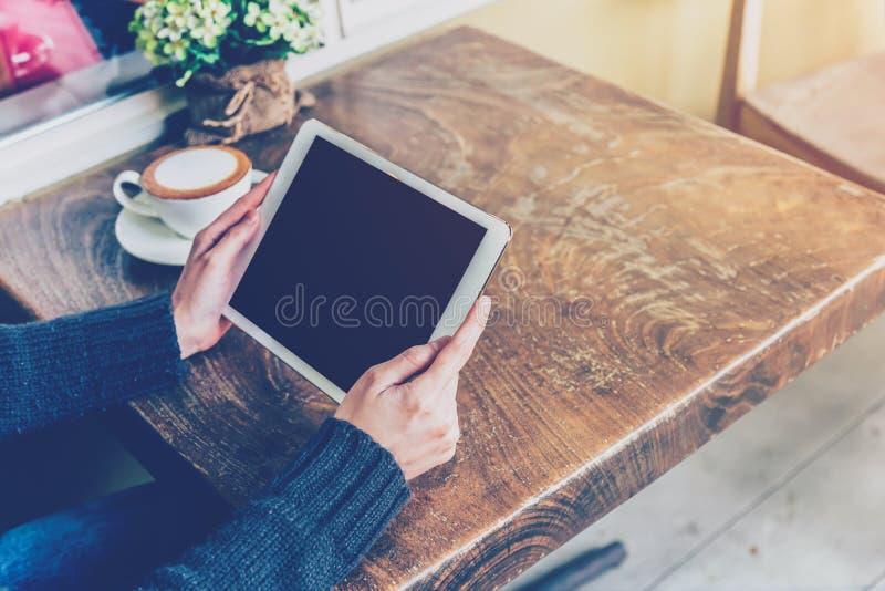Kvinna som använder minnestavlan i coffee shop arkivbilder