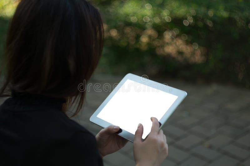 Kvinna som använder minnestavlan i trädgård royaltyfria bilder
