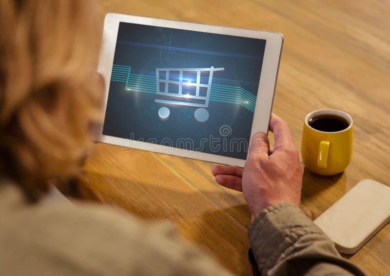 Kvinna som använder minnestavlan med shoppingspårvagnsymbolen royaltyfria foton