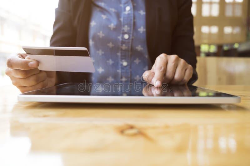 Kvinna som använder minnestavlan till online-shopping och lön vid kreditkorten fotografering för bildbyråer