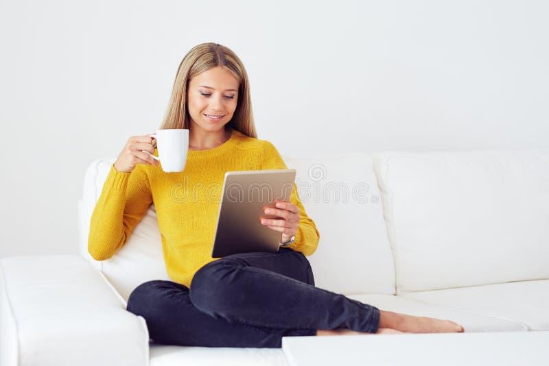 Kvinna som använder minnestavlasammanträde på soffan arkivfoto