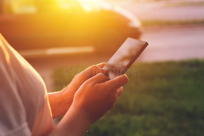 Kvinna som använder mobiltelefonen app för att kalla taxitaxin royaltyfri bild