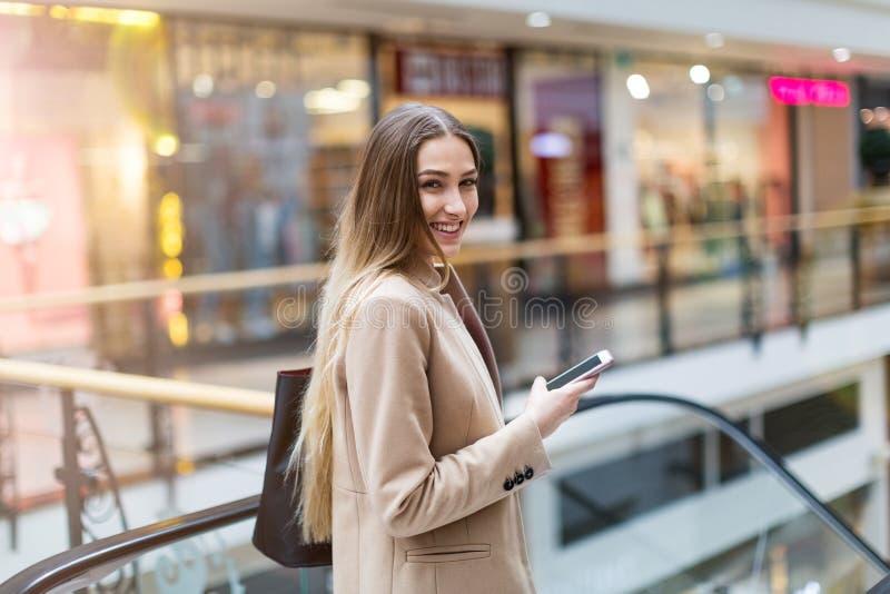Kvinna som använder mobiltelefonen i shoppinggalleria royaltyfri foto