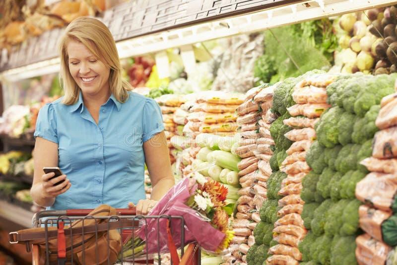 Kvinna som använder mobiltelefonen i supermarket royaltyfri bild