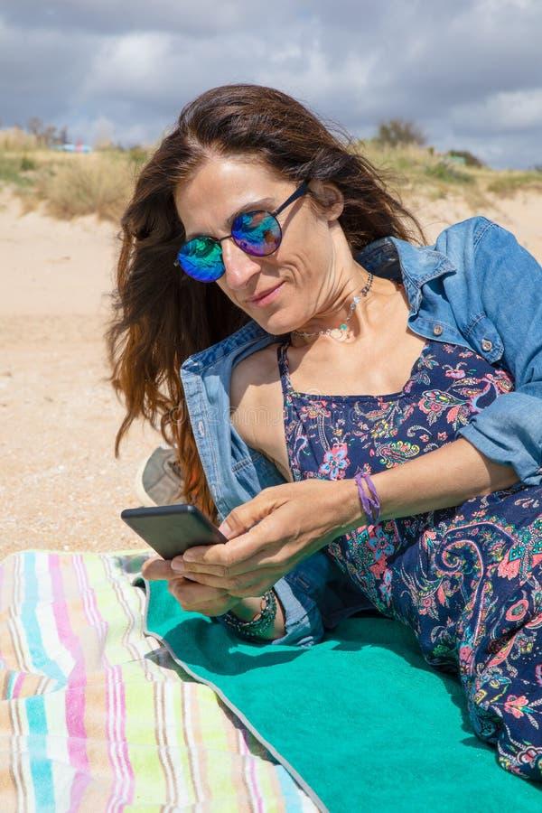 Kvinna som använder mobiltelefonen som ligger på handduken på stranden arkivbilder