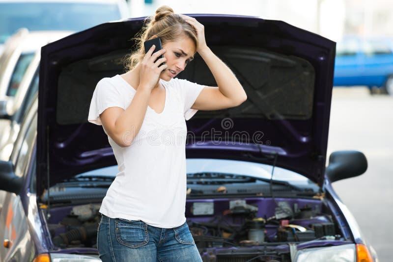 Kvinna som använder mobiltelefonen, medan se den brutna ner bilen royaltyfria bilder