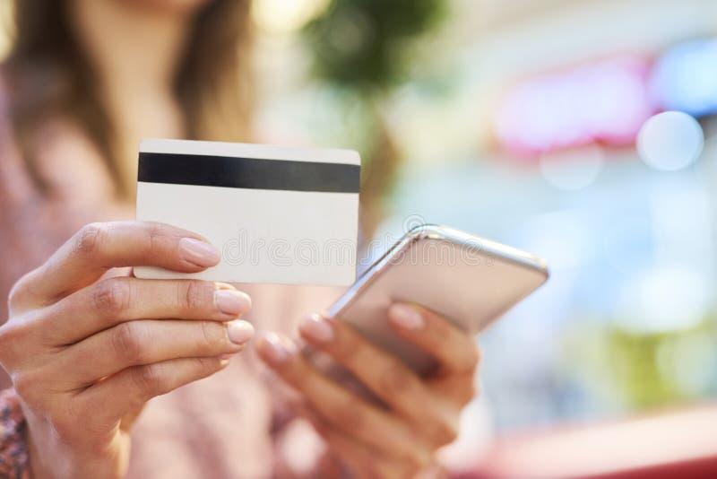 Kvinna som använder mobiltelefonen och kreditkorten under online-shopping royaltyfri bild