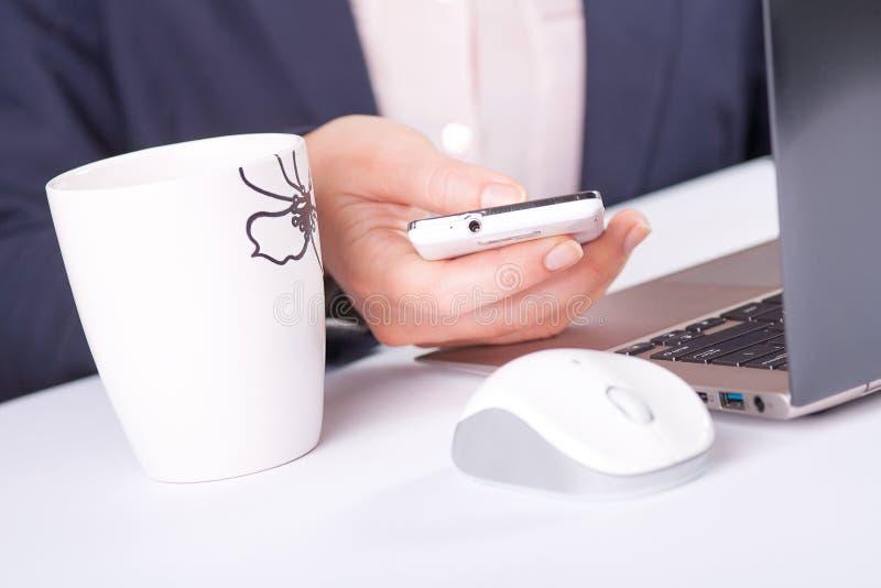 Kvinna som använder mobiltelefonen på arbete royaltyfri foto
