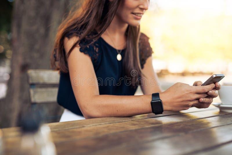 Kvinna som använder mobiltelefonen på kafét royaltyfri foto
