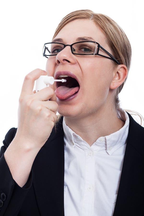 Kvinna som använder muntlig sprej royaltyfri fotografi