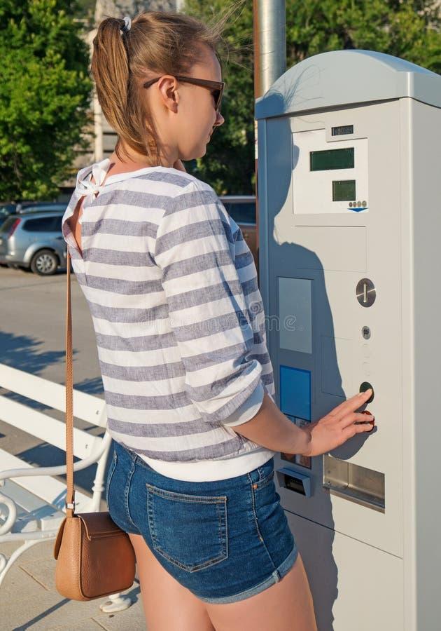 Kvinna som använder parkeringsmaskinen arkivbild