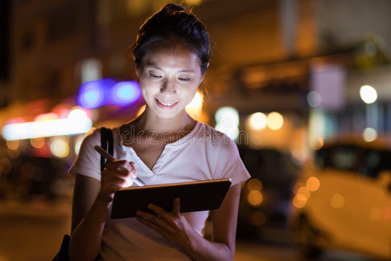 Kvinna som använder pennan på den digitala minnestavladatoren i stad på natten royaltyfria foton