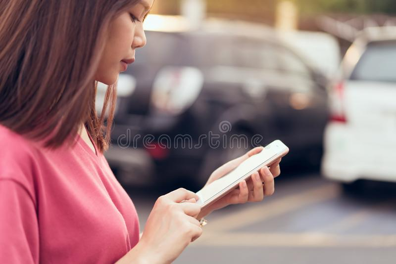 Kvinna som använder smartphonen för applikationen på bilsuddighetsbakgrund royaltyfri foto