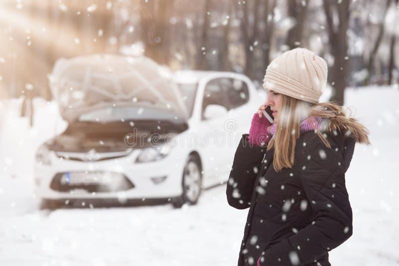 Kvinna som använder smartphonen för att kalla väghjälp Vinter och vehic royaltyfri fotografi