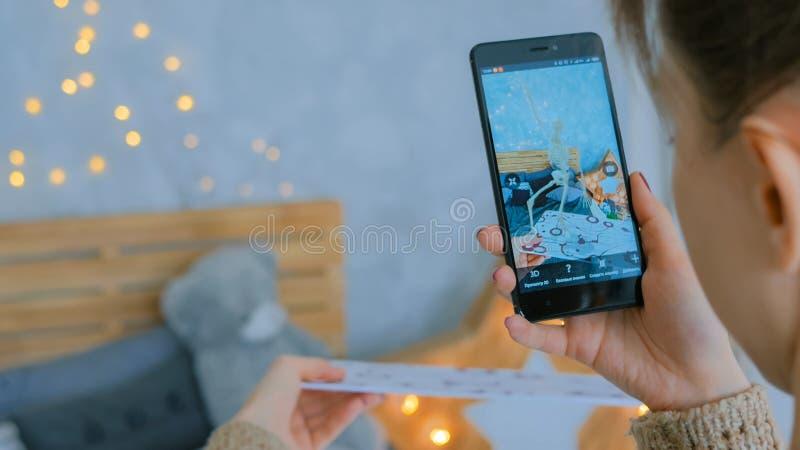 Kvinna som använder smartphonen med ökad verklighet app royaltyfri foto
