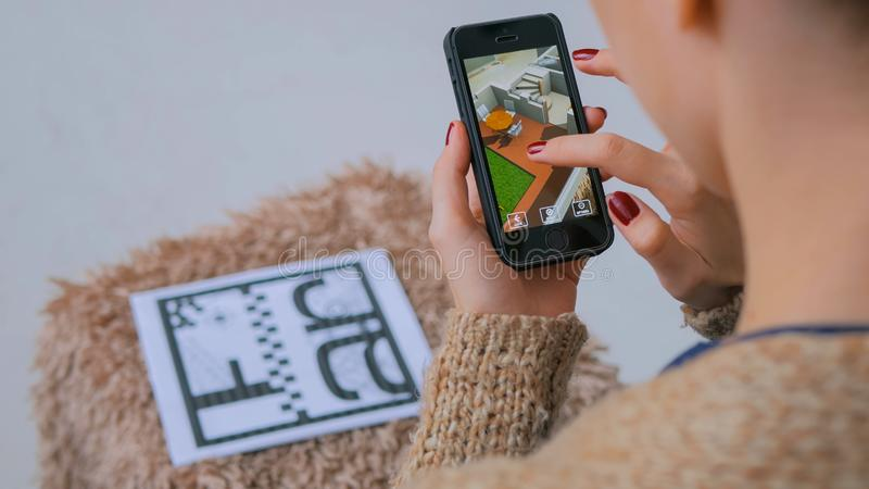 Kvinna som använder smartphonen med ökad verklighet app som kontrollerar faktiskt husplan arkivfoto