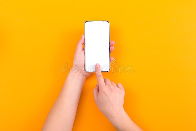 Kvinna som använder smartphonen med den tomma skärmen på orange bakgrund Top besk?dar royaltyfri foto