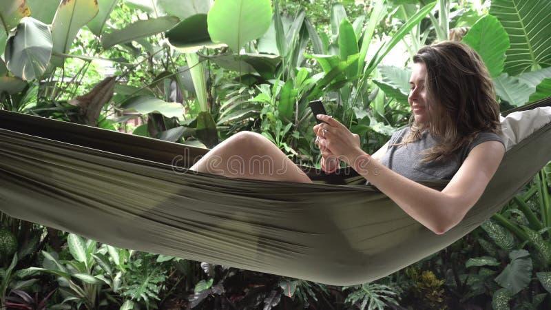 Kvinna som använder smartphonen, medan sitta på hängmattan, exotisk bakgrund arkivbild