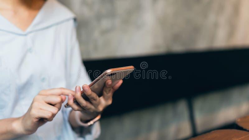 Kvinna som anv?nder smartphonen som smsar p? kaf?t kopieringsutrymme f?r annonser arkivfoton
