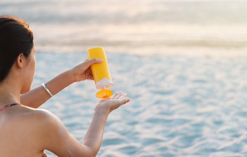 Kvinna som använder sollotion på stranden royaltyfri foto