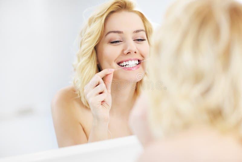 Kvinna som använder tandtråd royaltyfri foto