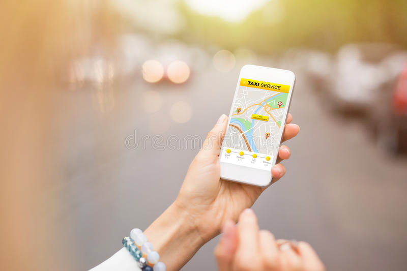 Kvinna som använder taxien app på mobiltelefonen arkivfoto