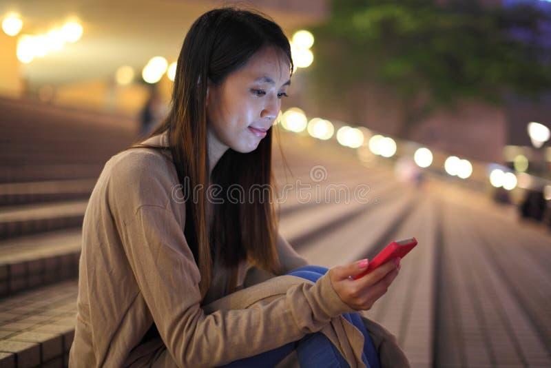 Kvinna som använder telefonen i stad arkivfoto