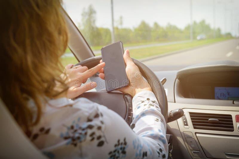 Kvinna som använder telefonen, medan köra bilen royaltyfria bilder