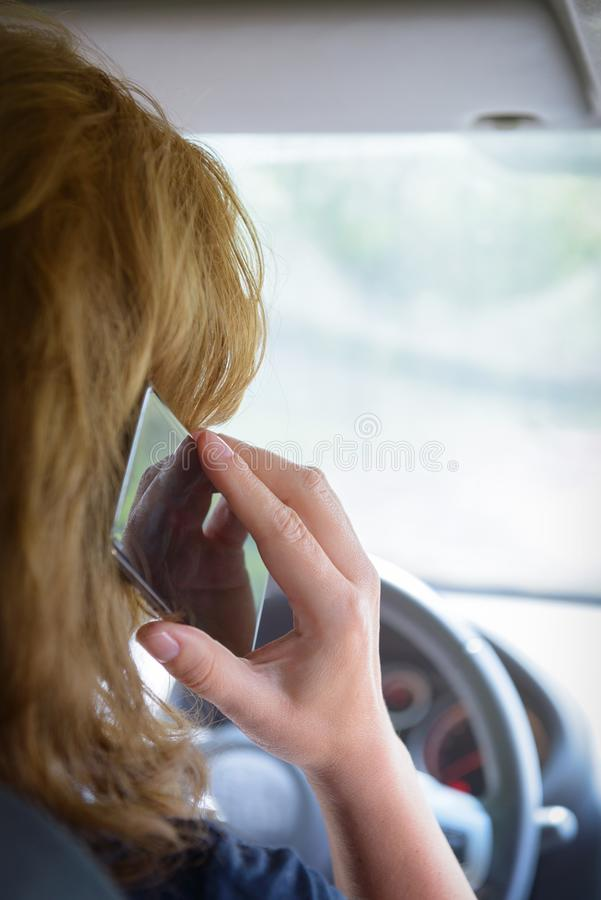 Kvinna som använder telefonen, medan köra bilen royaltyfri fotografi