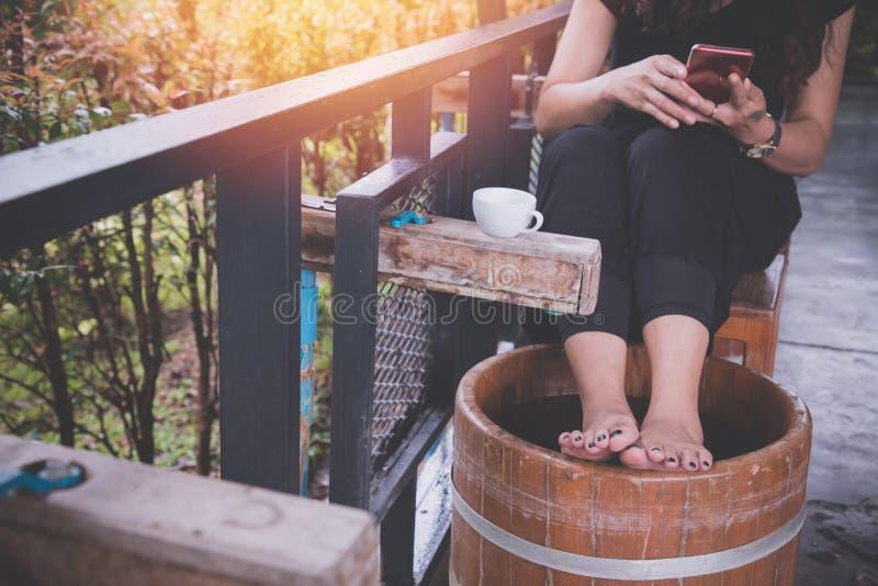 Kvinna som använder telefonen och foten som badar på trähinken av vatten, asiatisk kvinnalivsstil arkivbild