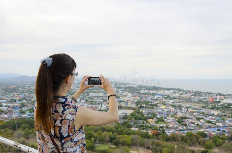 Kvinna som använder telefonen som tar bilder arkivfoton