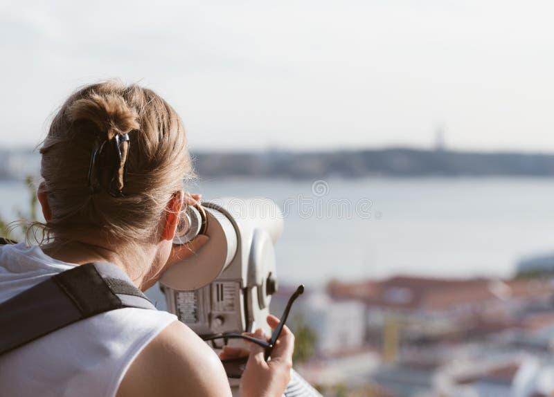 Kvinna som använder teleskopet arkivbild
