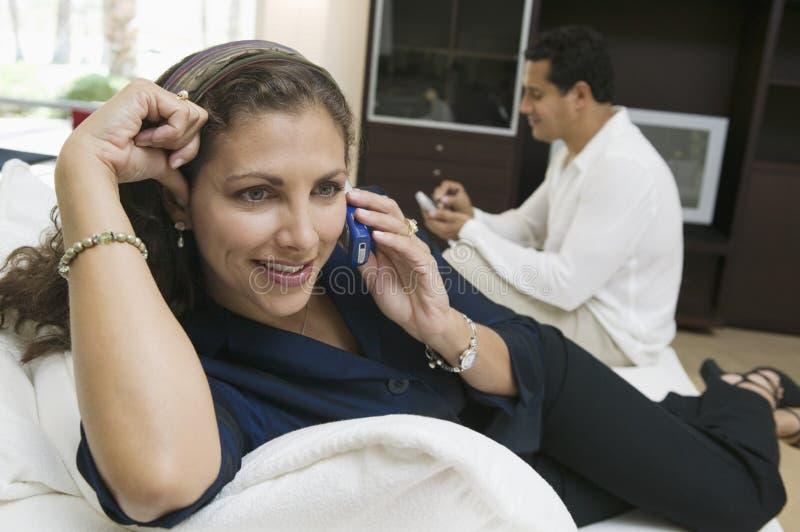 Kvinna som använder upp mobiltelefonen på soffaslut arkivbild