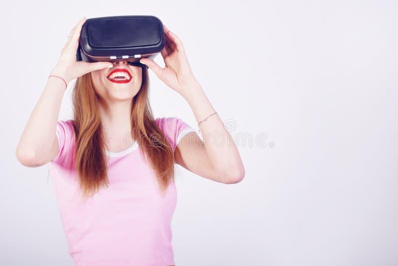 Kvinna som använder VR-hörlurar med mikrofon Härlig flicka, VR-erfarenhet som isoleras på vit Visuellt verklighetbegrepp Kvinna s arkivfoton