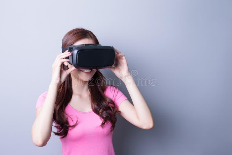 Kvinna som använder VR-hörlurar med mikrofonexponeringsglas arkivbild