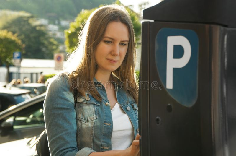 Kvinna som anv?nder parkeringsmaskinen arkivfoto