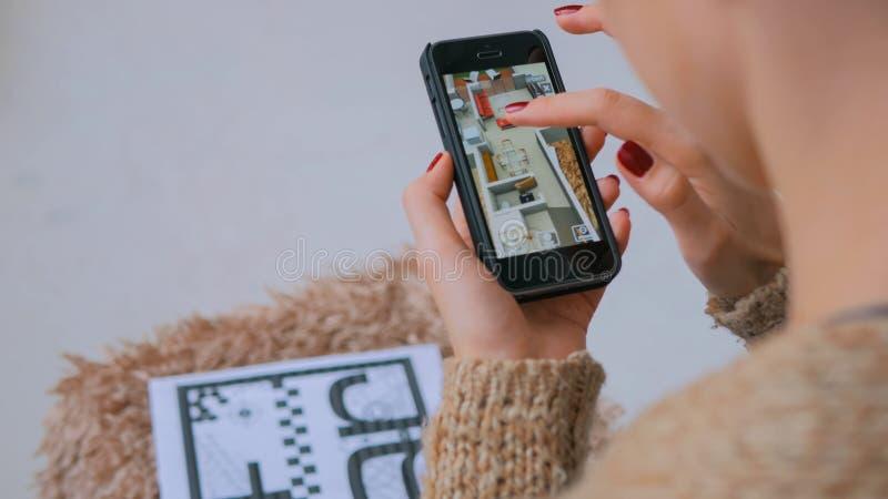 Kvinna som anv?nder smartphonen med ?kad verklighet app som kontrollerar faktiskt husplan arkivbilder