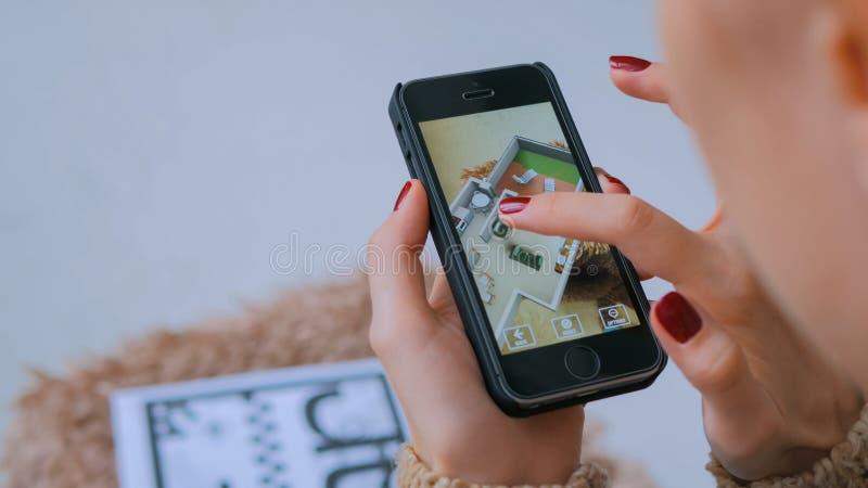 Kvinna som anv?nder smartphonen med ?kad verklighet app som kontrollerar faktiskt husplan royaltyfri foto
