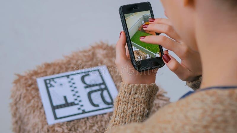 Kvinna som anv?nder smartphonen med ?kad verklighet app som kontrollerar faktiskt husplan arkivbild