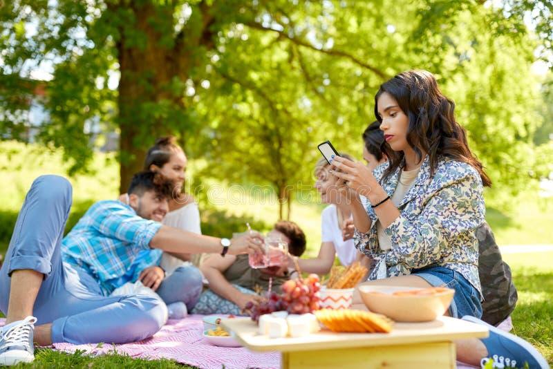 Kvinna som anv?nder smartphonen p? picknicken med v?nner arkivbilder
