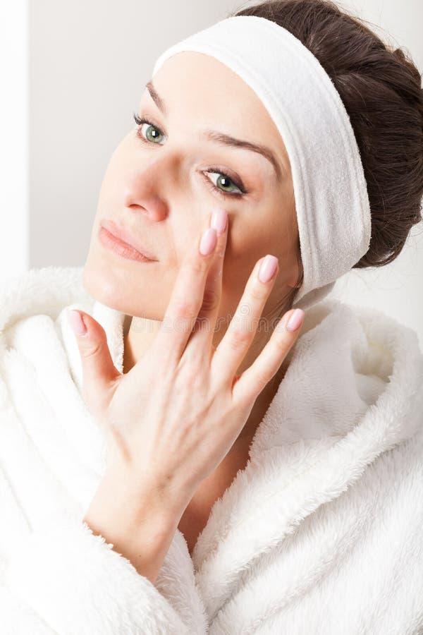 Kvinna som applicerar ögonkräm arkivfoton