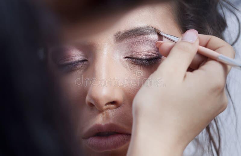 Kvinna som applicerar ögonmakeup royaltyfri foto