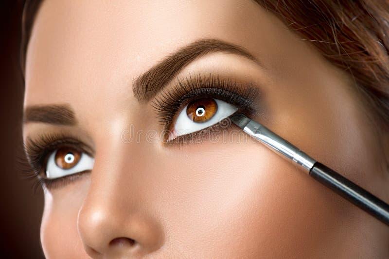 Kvinna som applicerar ögonmakeupcloseupen fotografering för bildbyråer