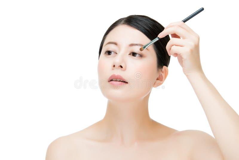 Kvinna som applicerar ögonskugga med makeupborsten asiatiskt skönhetbegrepp royaltyfri bild