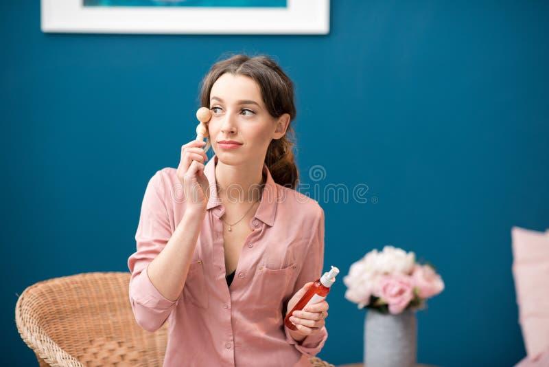 Kvinna som applicerar ansikts- massage arkivbilder