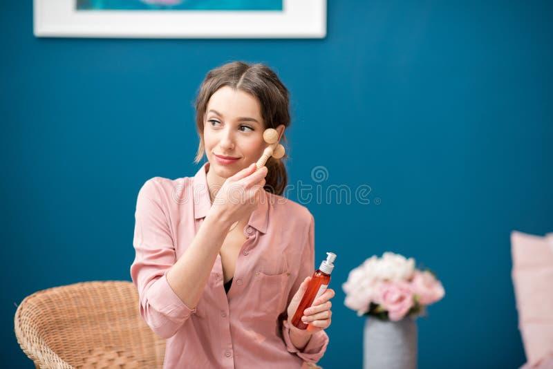 Kvinna som applicerar ansikts- massage royaltyfri bild