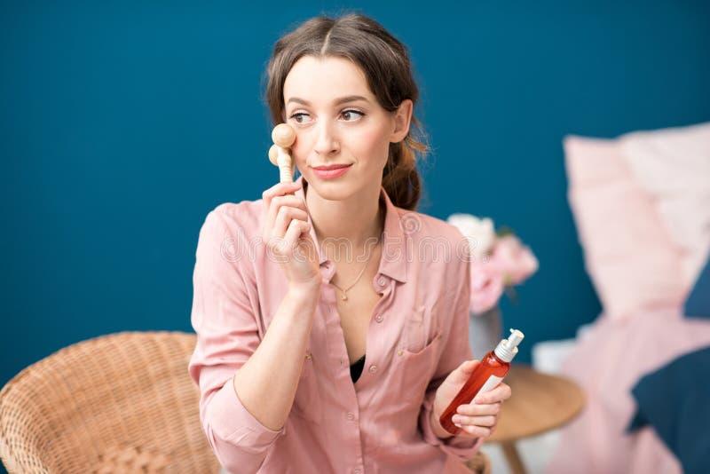 Kvinna som applicerar ansikts- massage royaltyfri foto