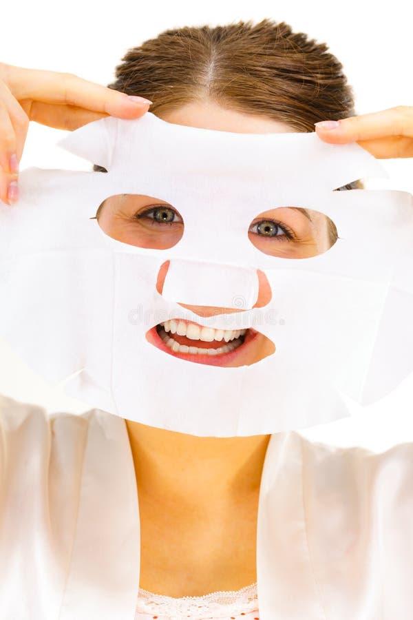Kvinna som applicerar arkmaskeringen p? framsida royaltyfria bilder